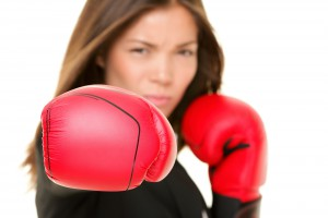 Boxing business woman punching towards camera wearing boxing glo